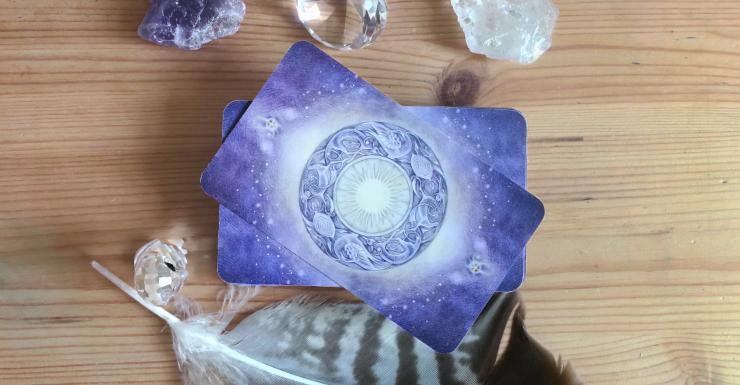 Ein Stapel Orakelkarten zwischen Kristallen.